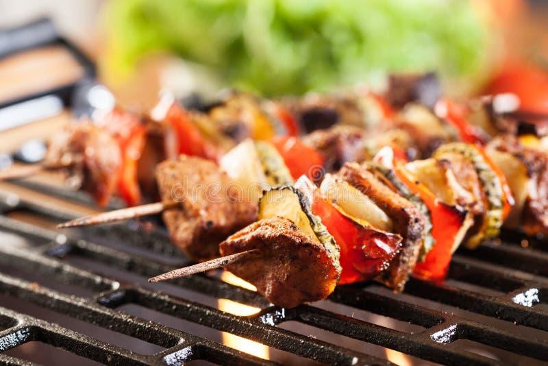 Grilling shashlik on barbecue grill stock image