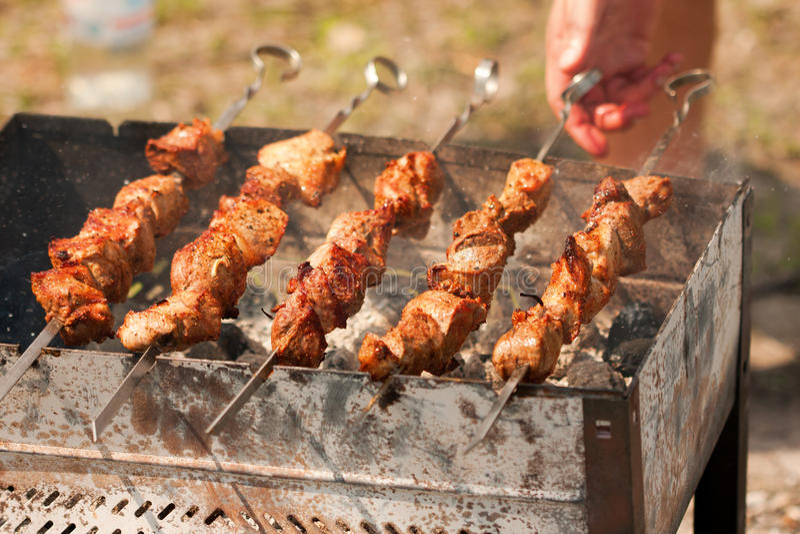 Grilling shish kebabin in brazier. Man grilling juicy shish kebabin in brazier stock photos