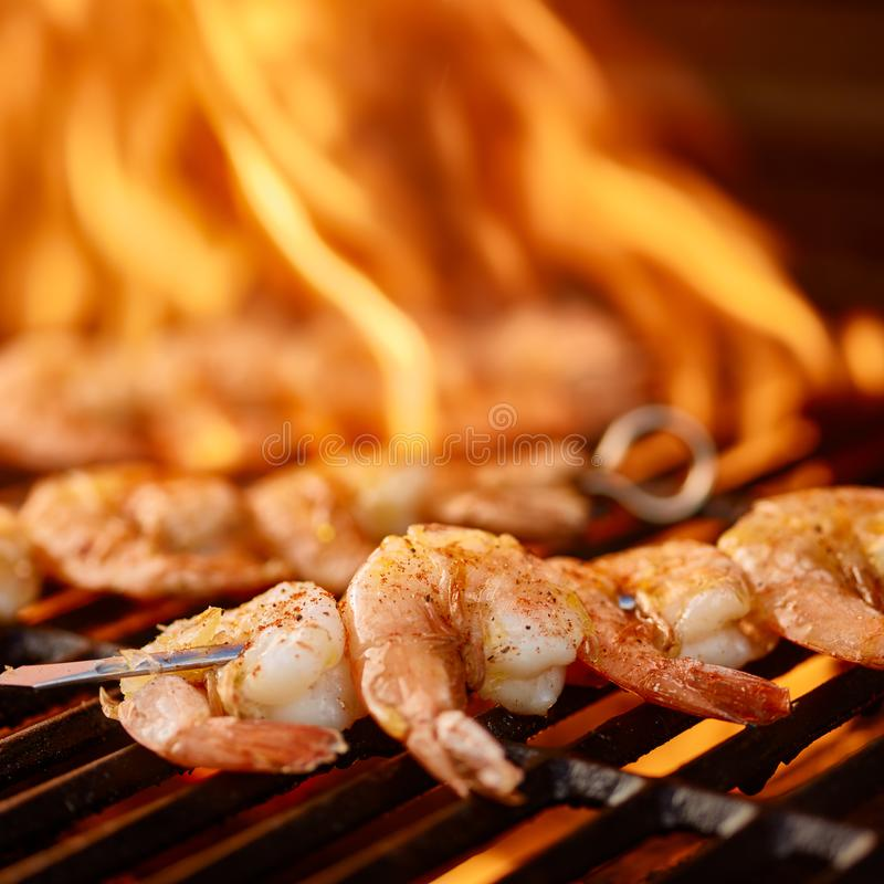 Grilling shrimp on skewer on grill. With flames royalty free stock image