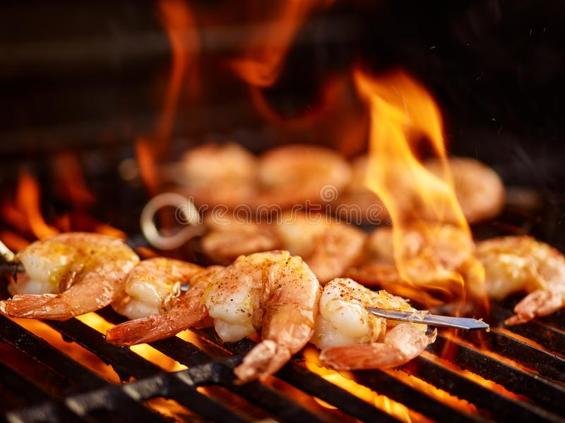 Grilling shrimp on skewer on grill. With flames stock image