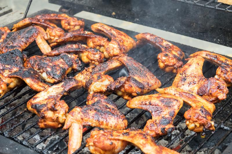 Grilling spicy chicken wings on barbecue grill stock images