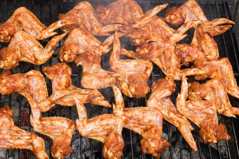 Grilling spicy chicken wings on barbecue grill. stock photos