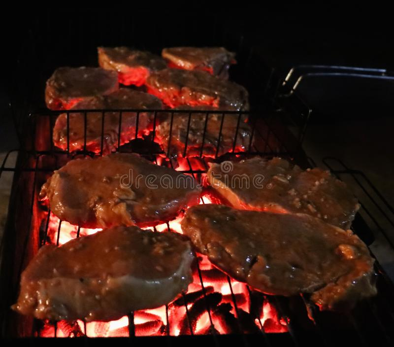 Grilling steaks on flaming grill stock photos