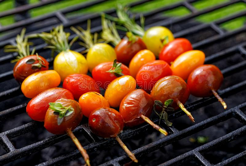 Grilling tomato skewers, skewers of colorful cherry tomatoes studded on rosemary sprigs with the addition of aromatic spices and s. Ea salt on a grill plate royalty free stock photo