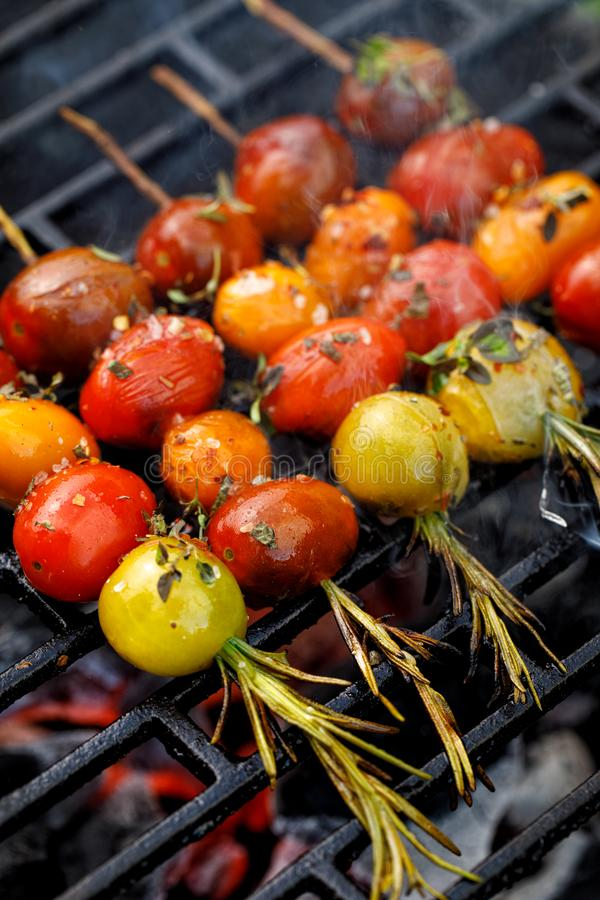 Grilling tomato skewers, skewers of colorful cherry tomatoes studded on rosemary sprigs with the addition of aromatic spices and s. Ea salt on a grill plate royalty free stock photos