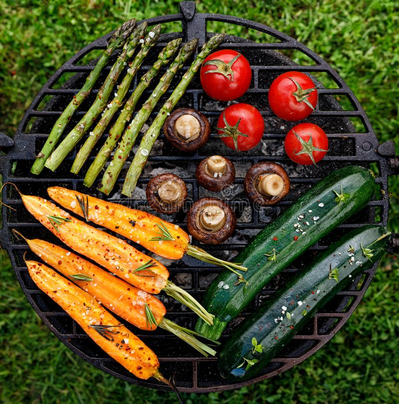 Grilling vegetables with the addition of spices and herbs on the grill plate outdoors, top view. Vegan grilled food, barbecue grill royalty free stock images