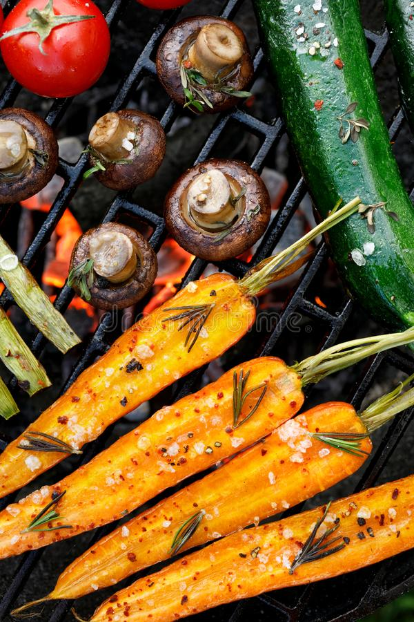 Grilling vegetables with the addition of spices and herbs on the grill plate outdoors, top view. Vegan grilled food, barbecue grill stock photo
