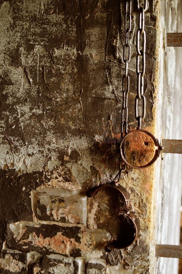 Grillos viejos del metal en las manos en la prisión antigua imagenes de archivo