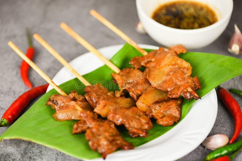 Grilltes Schweinefleisch thai asianisch auf der Straße Küche - Skewer-Stöcke aus Slice gegrillt auf Bananenblatt auf weißem Telle lizenzfreie stockfotos