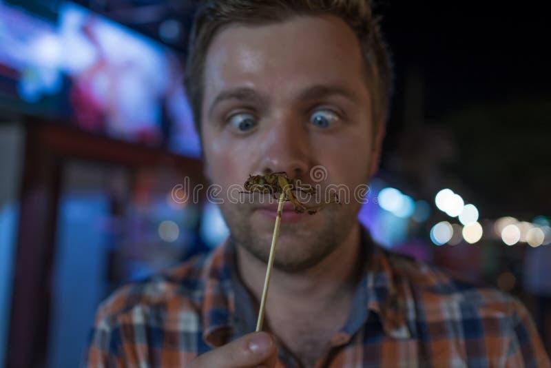 Grilo masculino novo caucasiano comer no mercado da noite em Tailândia imagens de stock