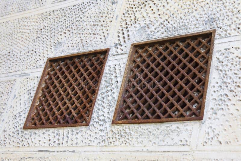 Grils de ventilation de fonte contre un mur de plâtre image stock