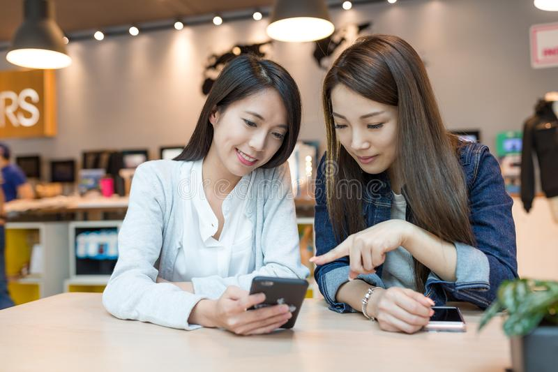 Grils Friends talking together with cellphone royalty free stock photo