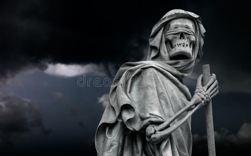 The Grim Reaper Death personified statue wanders in the dark night. The blindfolded Grim Reaper wanders in the dark night stock photos