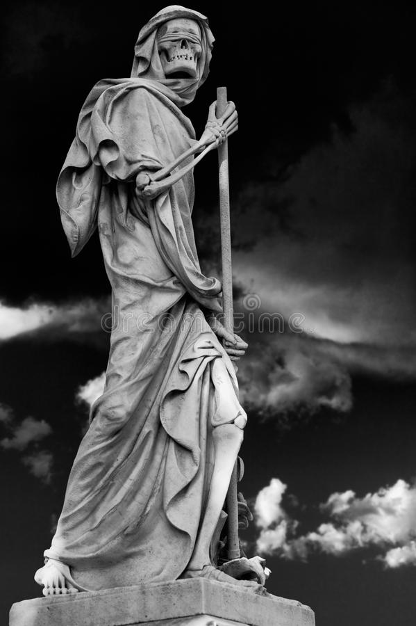 The Grim Reaper Death personified statue wanders in the dark night. The blindfolded Grim Reaper wanders in the stormy night stock photos