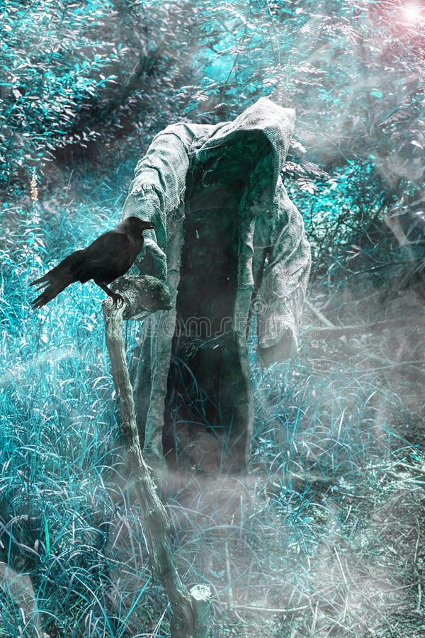 A grim reaper / ghost / witch in a long hood  in the middle of the dark woods. Scary and creepy person with hood standing in blue forest and holding stick of stock photo
