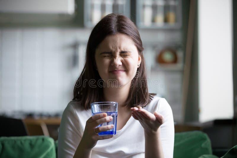 Grimacer soumis à une contrainte frustrant de jeune femme effrayé de prendre la pilule photos stock