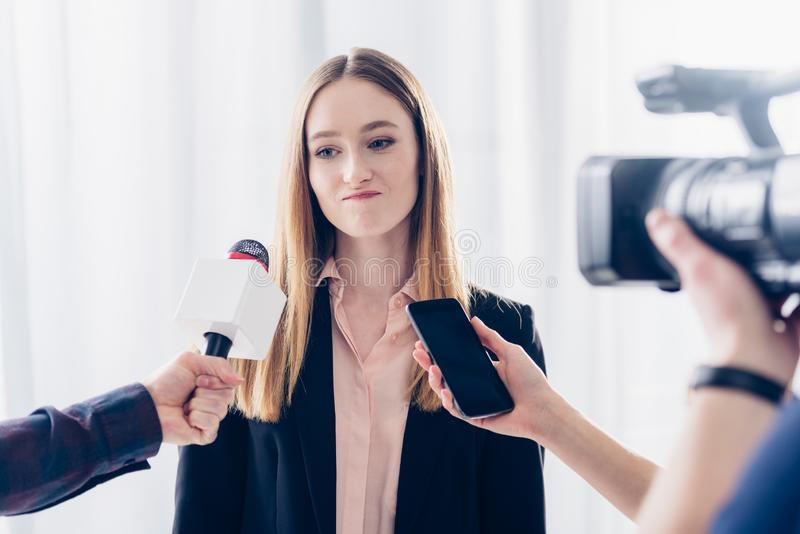 Grimacing businesswoman giving interview to journalists. In office stock images