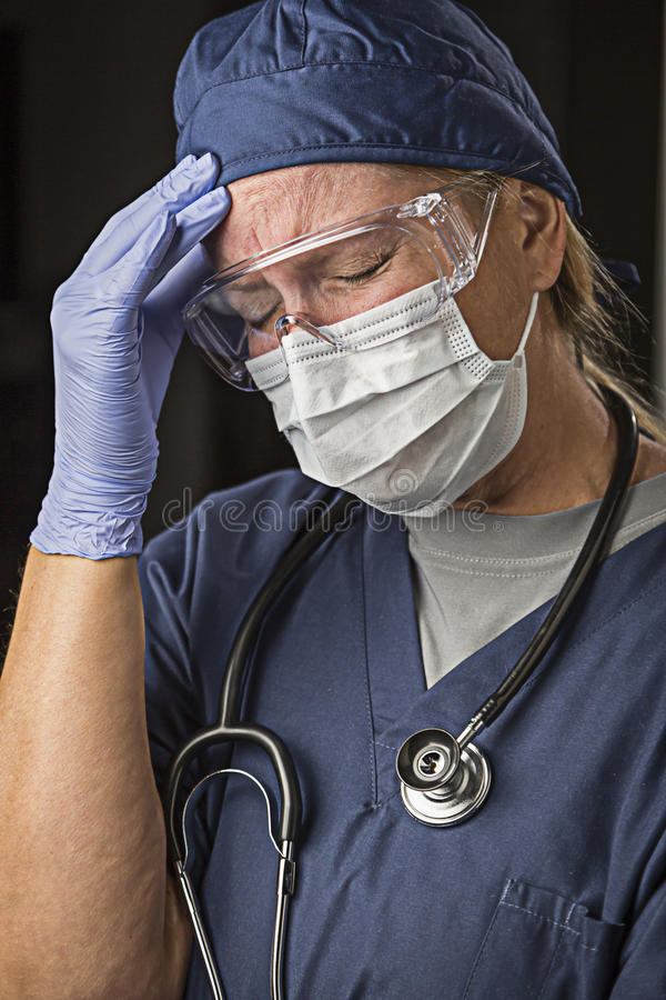 Grimacing Female Doctor or Nurse Wearing Protective Wear. Grimacing Female Doctor or Nurse Wearing Protective Facial Wear and Surgical Gloves stock photos