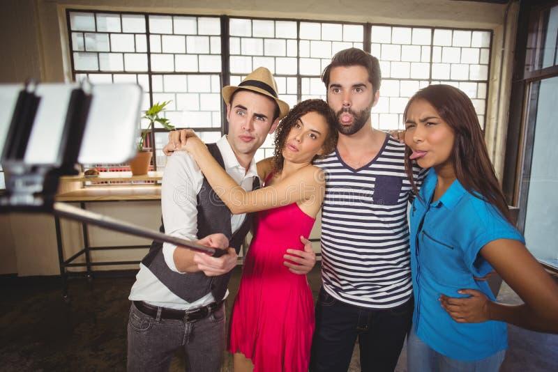 Grimassen trekkende vrienden die selfies met selfiestick nemen royalty-vrije stock afbeeldingen