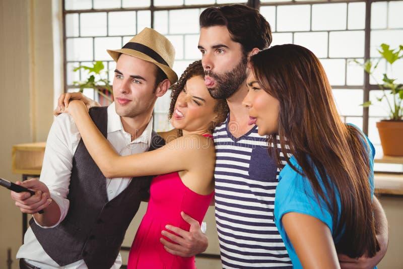 Grimassen trekkende vrienden die selfies met selfiestick nemen royalty-vrije stock fotografie