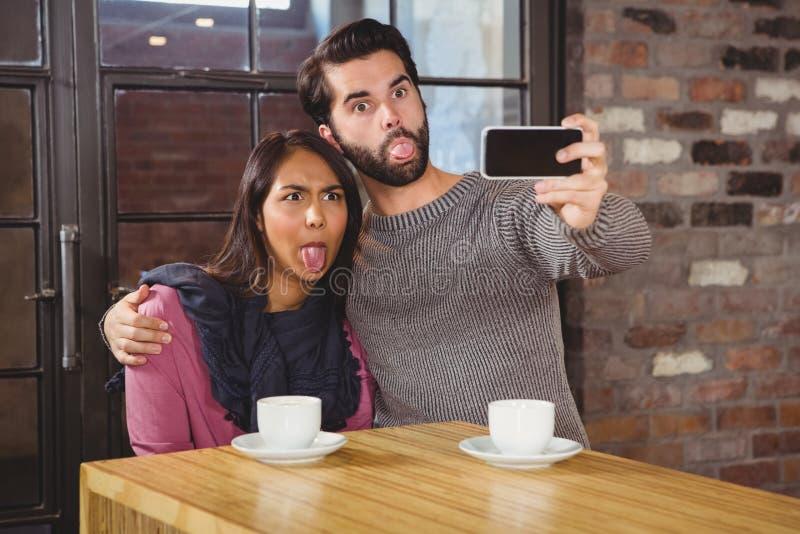 Grimassen trekkende vrienden die selfies nemen royalty-vrije stock afbeeldingen