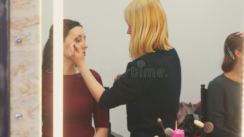 Grimeur aan het werk met het model in de spiegelbezinning royalty-vrije stock foto