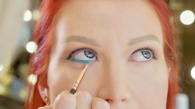 Grimeur die make-up toepassen om het oog van ` te modelleren s Sluit omhoog mening stock foto