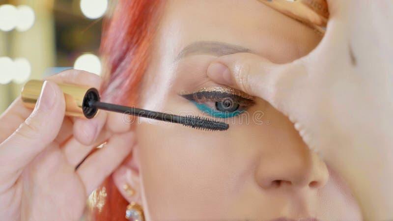 Grimeur die make-up toepassen om het oog van ` te modelleren s Sluit omhoog mening stock fotografie