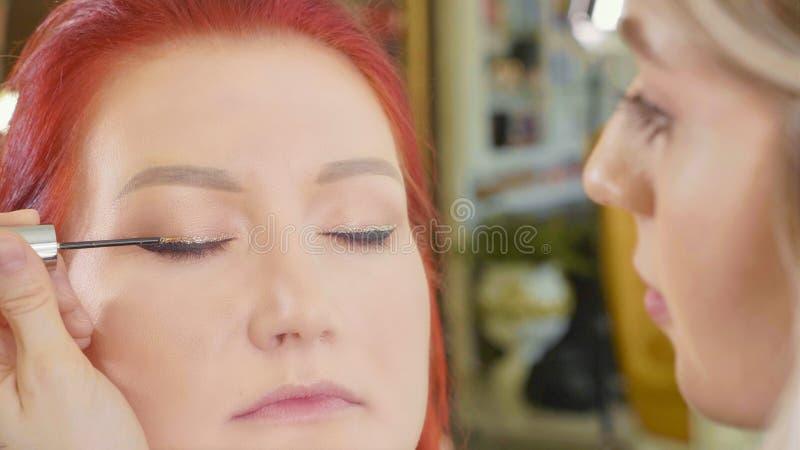 Grimeur die make-up toepassen om het oog van ` te modelleren s Sluit omhoog mening stock afbeeldingen