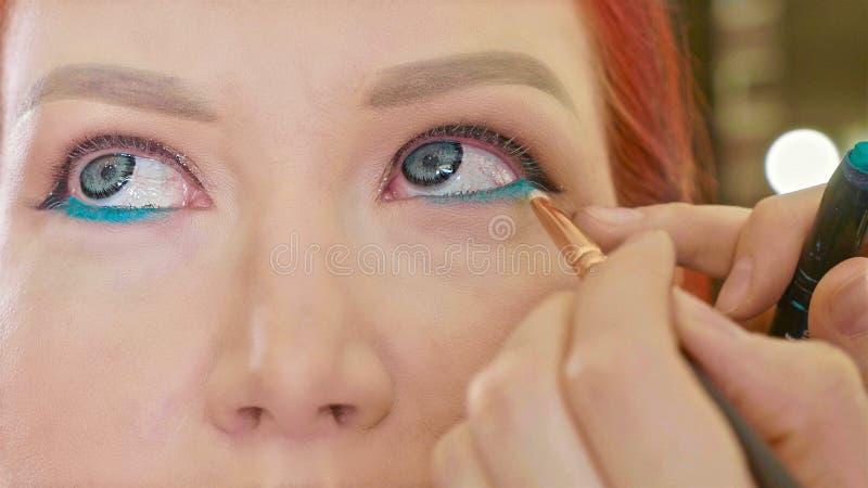 Grimeur die make-up toepassen om het oog van ` te modelleren s Sluit omhoog mening stock afbeelding