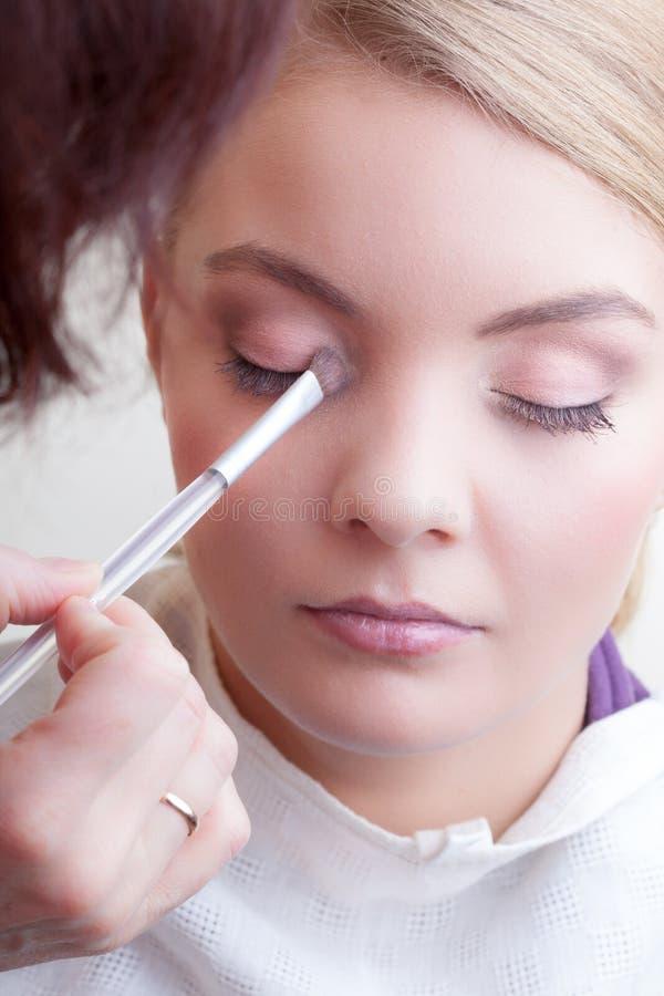 Grimeur die met de oogschaduw van de borstelkleur op vrouwelijk oog van toepassing zijn stock afbeelding