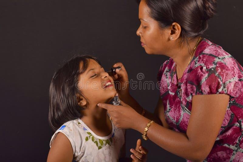 Grimeur die oogschaduw op een klein meisje, Pune toepassen royalty-vrije stock fotografie