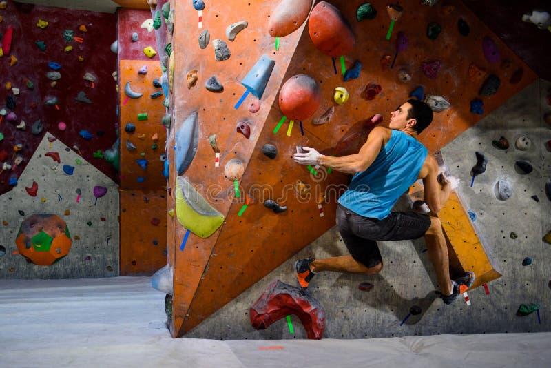 Grimpeur d'homme dans le gymnase bouldering Exercice d'intérieur de séance d'entraînement images stock