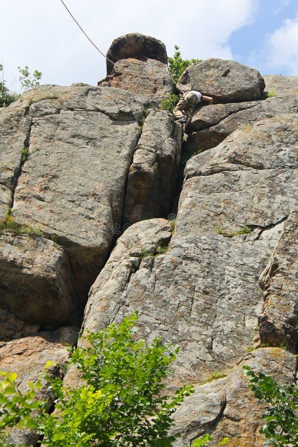 Grimpeur d'homme s'élevant sur une roche image stock