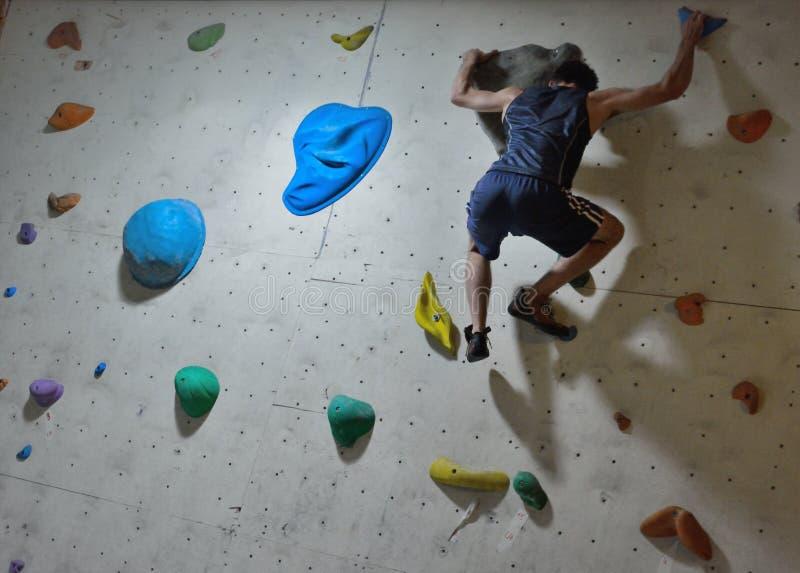 Grimpeur dans l'action, concentration avant un saut difficile photo stock
