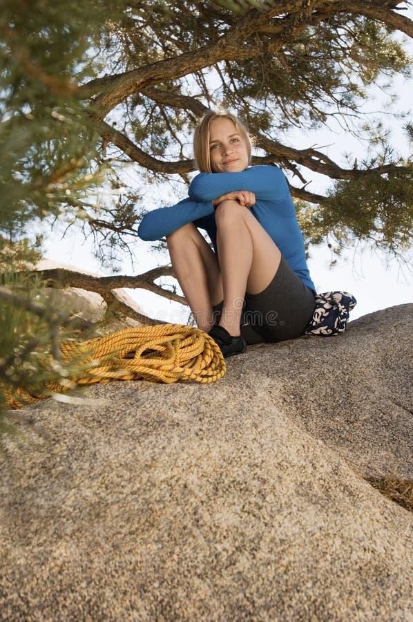 Grimpeur de femme s'asseyant sur le rocher photos stock
