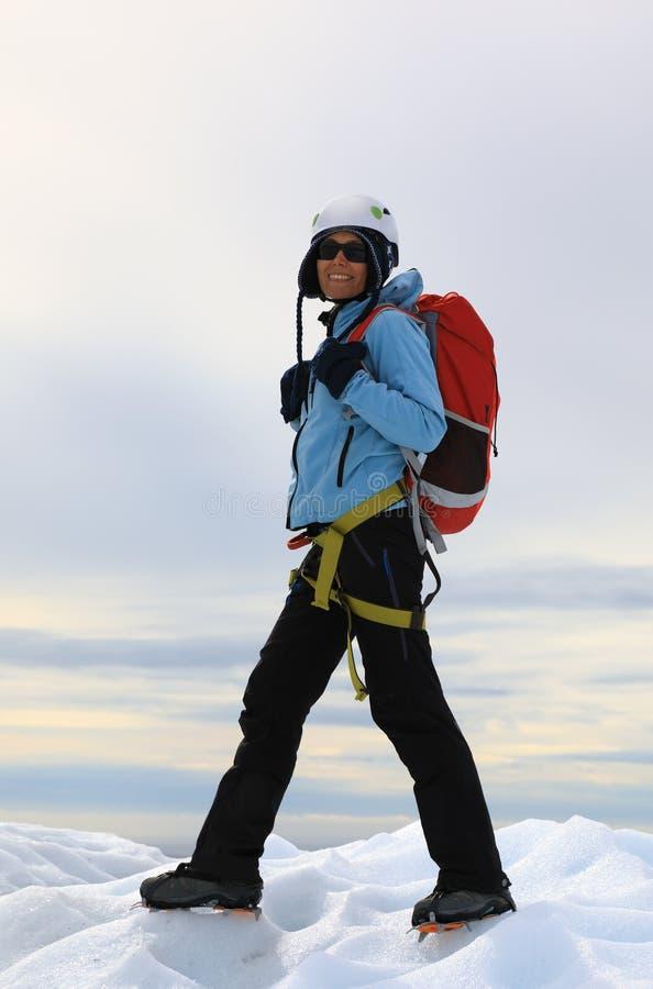 Grimpeur de femme se tenant sur le dessus glacial du glacier photographie stock libre de droits