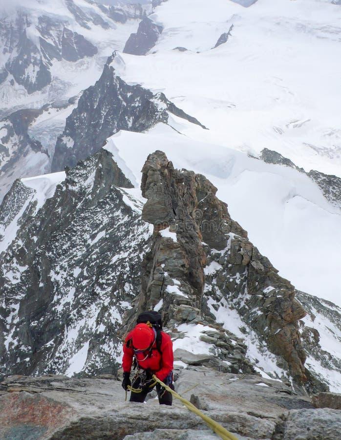 Grimpeur de montagne rappelling outre d'une crête alpine élevée rocheuse et de neige image libre de droits