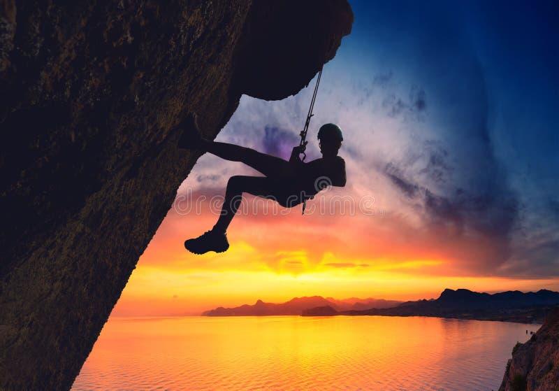 Grimpeur de roche contre le coucher du soleil image stock