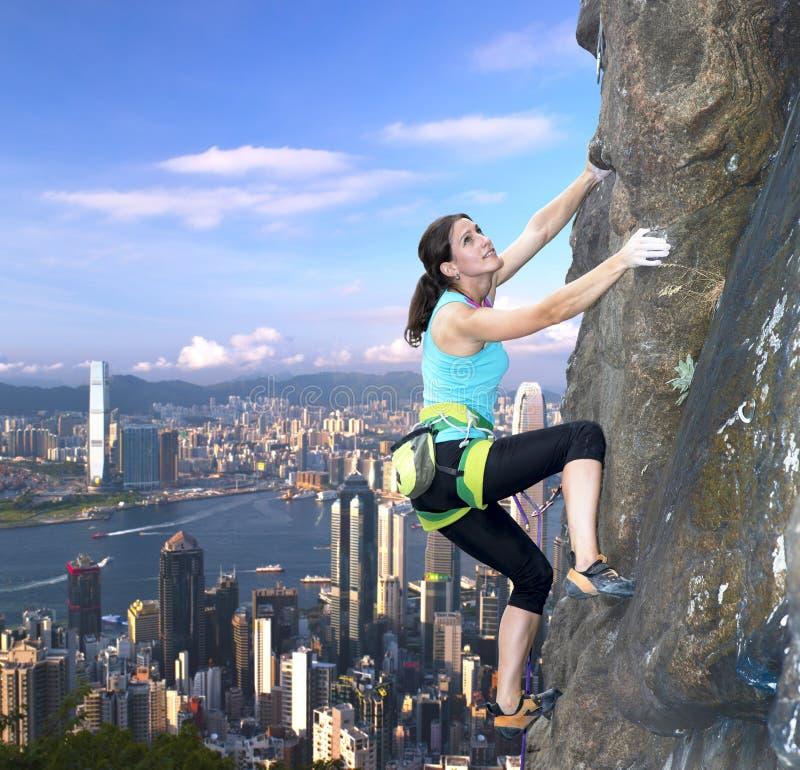 Grimpeur de roche féminin au-dessus de l'horizon de ville images stock