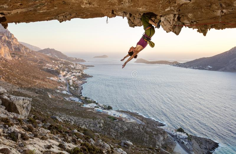 Grimpeur de roche féminin se reposant tout en accrochant à l'envers sur l'itinéraire exaltant en caverne au coucher du soleil image libre de droits