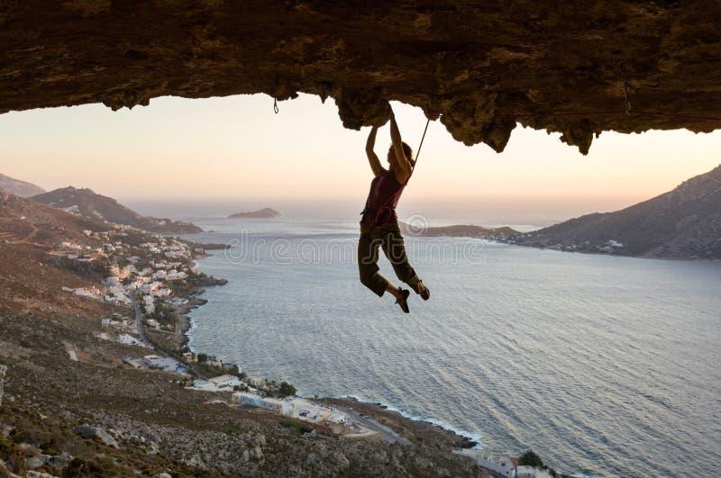 Grimpeur de roche féminin sur l'itinéraire exaltant en caverne au coucher du soleil images stock