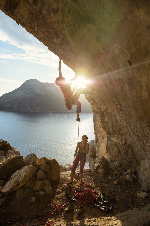 Grimpeur de roche masculin commençant contestant l'itinéraire sur la falaise au coucher du soleil, grimpeur féminin l'assiégeant photos stock
