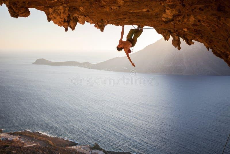 Grimpeur de roche masculin s'élevant le long d'un toit dans une caverne photos libres de droits