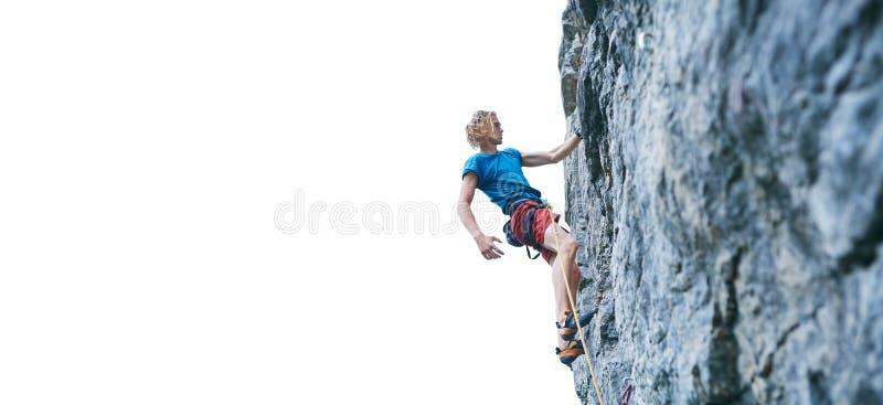 Grimpeur de roche masculin se reposant tout en montant l'itinéraire provocant sur le mur rocheux images stock
