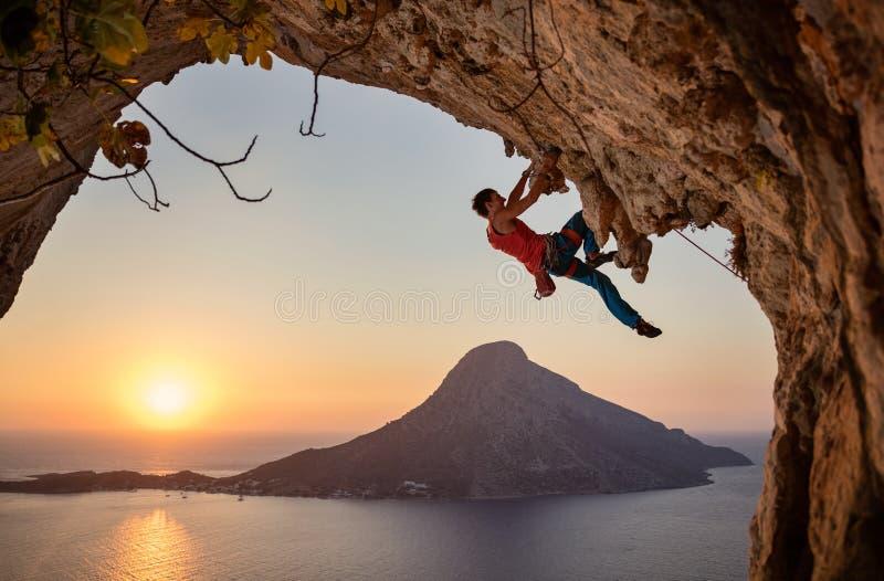 Grimpeur de roche masculin sur l'itinéraire exaltant sur la falaise au coucher du soleil image libre de droits
