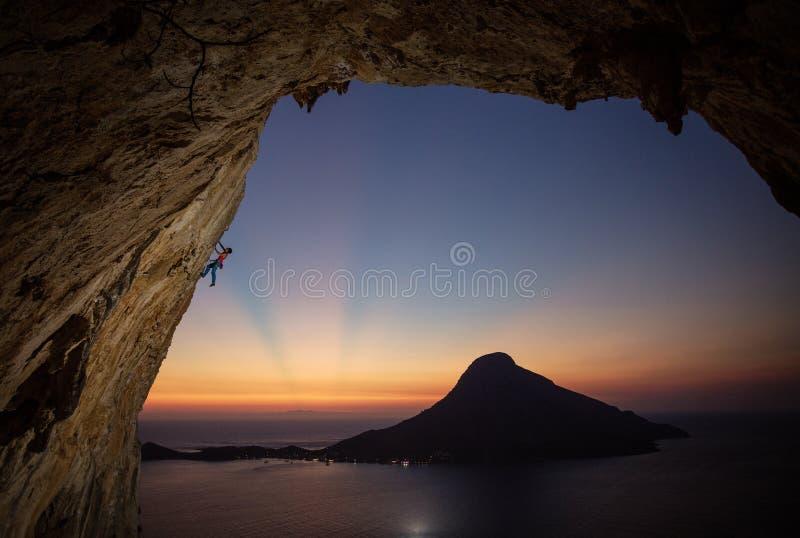 Grimpeur de roche masculin sur la falaise surplombante au coucher du soleil, avec la belle vue de l'île à l'arrière-plan photos libres de droits