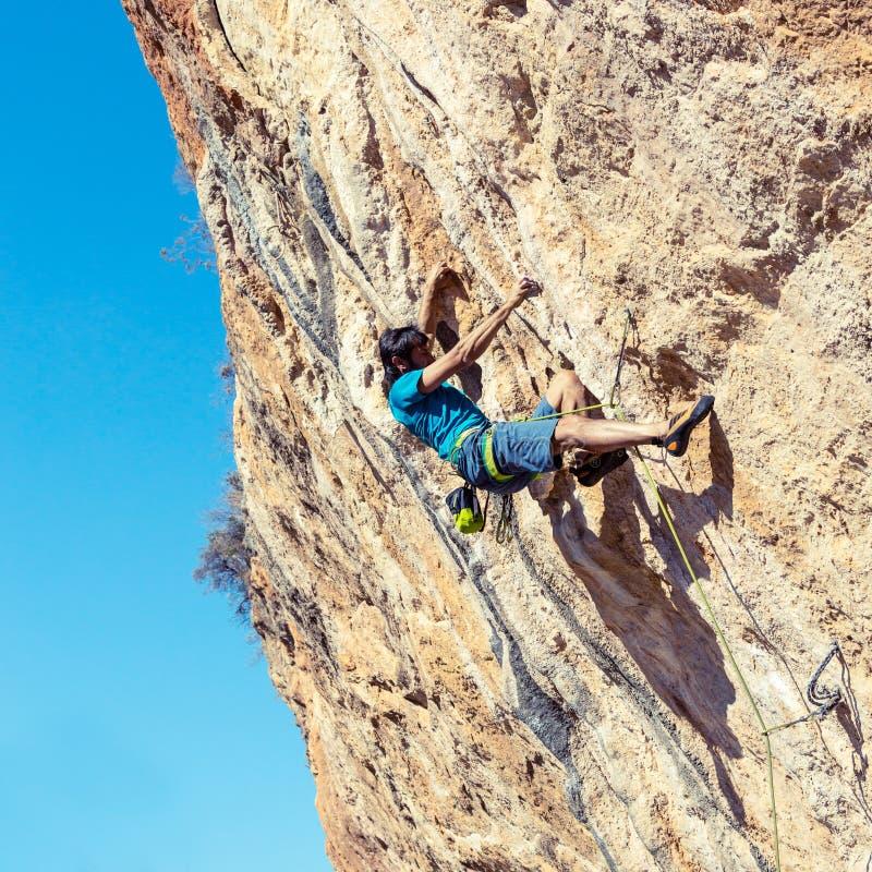 Grimpeur de roche masculin sur le haut mur photographie stock