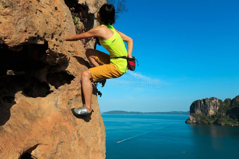 Grimpeur de roche s'élevant à la falaise de bord de la mer photo stock