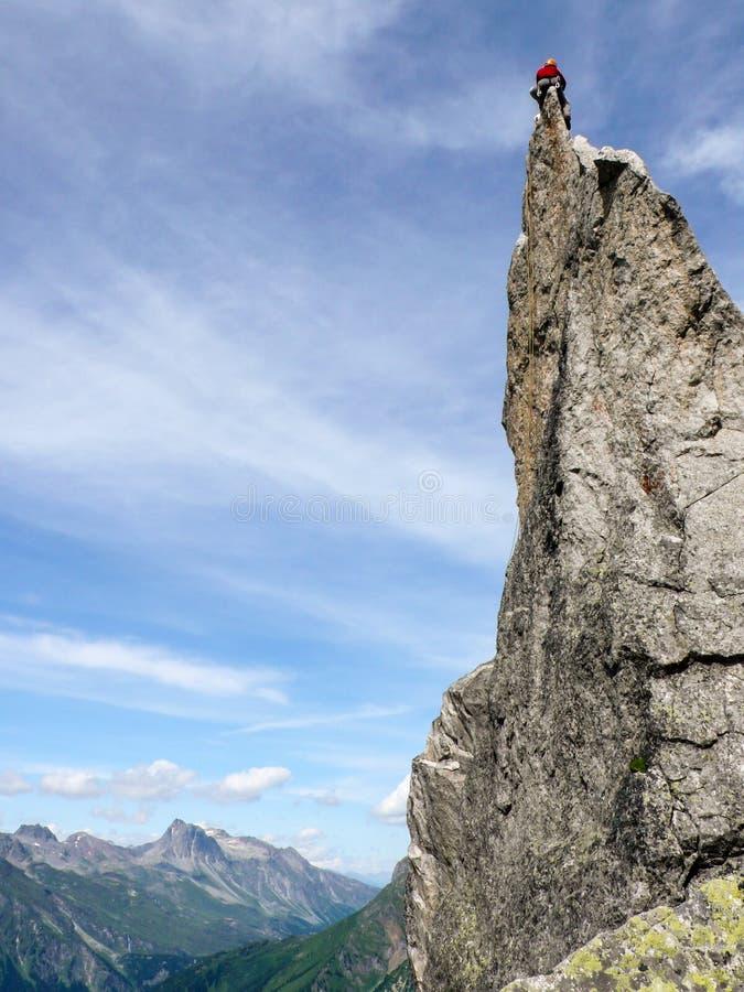Grimpeur de roche s'asseyant placé sur une aiguille pointue de roche dans Val Bregaglia photographie stock